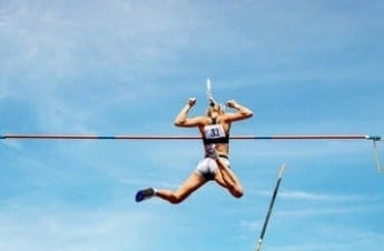Woman Jumping over a high bar. She uses CBD for sports.