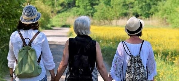Three ladies in their 60's holding hands walking on a nature trail. They use Stirling CBD to reduce pain and inflammation.