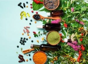 CBD Capsules and other ingredients on a table, including turmeric, berries and lavender.